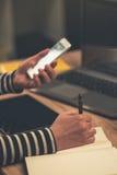 Nombres de contactos de la escritura de la empresaria y números de teléfono en notebo imágenes de archivo libres de regalías