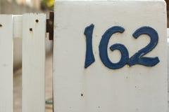 Nombres de maison bleus métalliques sur le picke blanc Photos stock
