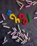 Nombres et lettres colorés de craies sur le tableau noir Images stock