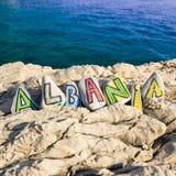 Nome di paese dell'Albania sulle pietre, paesaggio con il mare nei precedenti Fotografia Stock Libera da Diritti