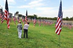 Nome di sguardo delle donne di una vittima di 9-11 sulla bandierina degli Stati Uniti Immagini Stock