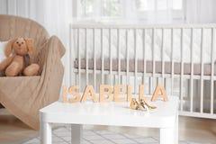 Nome ISABELLA del bambino composta di lettere di legno sulla tavola immagini stock libere da diritti