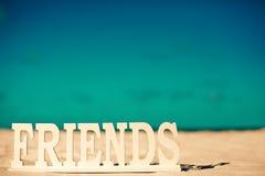 Nommez les amis sur le sable blanc derrière le ciel bleu Photos stock