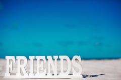 Nommez les amis sur le sable blanc derrière le ciel bleu Image stock