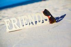 Nommez les amis sur le sable blanc derrière le ciel bleu Photographie stock libre de droits