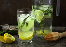 Non-alcoholic drink cocktail of fresh fruits: cucumber, lime, rosemary. Concept of a healthy drink. Rusty metal background Stock Image