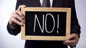 Non avec la marque d'exclamation écrite sur le tableau noir, homme d'affaires tenant le signe Images libres de droits