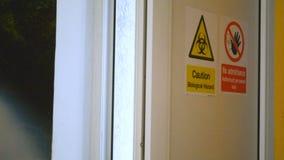 Non avverta il rischio biologico e segni d'avvertimento del pericolo di entrata sull'entrata della porta al laboratorio archivi video