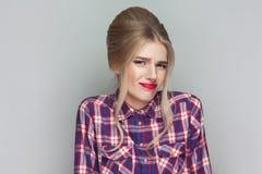 Non so bella ragazza confusa con la camicia a quadretti rosa, immagine stock