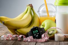 Non-caloric food for staying fit. And with great curves. Sports watch to keep a training organized, tape-measure to look after the waist and tasty fruits with a royalty free stock photo