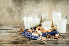 Non-dairy milk food concept. Plant based vegan food and drink, Non-dairy milk and cheese tofu - from almond, nuts, soy beans, oats and coconut, wooden background stock photography