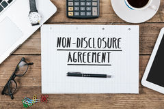 Non-diclosure agreement on notebook on Office desk with computer. Words non-disclosure agreement on notebook, Office desk with electronic devices, computer and Royalty Free Stock Photography
