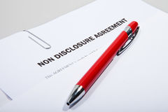 Non disclosure agreement and pen. Non disclosure agreement showing out of white envelope with pen Stock Photos