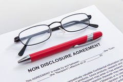 Non disclosure agreement and pen. Non disclosure agreement showing out of white envelope with pen Royalty Free Stock Photo