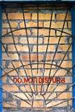 Non disturbi il contrassegno sulla finestra mattone-incassata Fotografia Stock Libera da Diritti