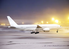 Non-flying weather in airport. White plane in airport at non-flying weather, snow-storm Royalty Free Stock Photo
