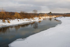 Non-freezing river on winter forest backgrounds. Non-freezing river on a winter forest backgrounds Stock Photo