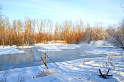 Non-freezing winter lake. Bare winter trees near the pond above which steam rises. Winter. Russia. Abakan royalty free stock photos