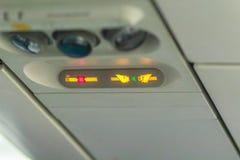 Non-fumeurs et attachez le signe de ceinture de sécurité à l'intérieur d'un avion attachez Image libre de droits