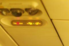 Non-fumeurs et attachez le signe de ceinture de sécurité à l'intérieur d'un avion attachez Images stock