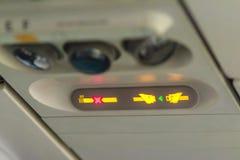 Non-fumeurs et attachez le signe de ceinture de sécurité à l'intérieur d'un avion attachez Images libres de droits