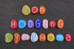 Non-Hodgkin Lymphoma text composed with multi colored stones over black volcanic sand stock photography