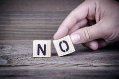 Non Lettres en bois sur le fond de bureau, instructif et de communication Photo stock