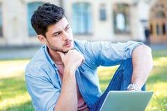 Non metta l'esame Studente bello del tipo che tiene un computer portatile e una h Fotografia Stock Libera da Diritti