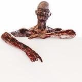 Non morto dello zombie che tiene una carta in bianco del segno della pubblicità su un fondo bianco isolato con stanza per lo spaz Fotografie Stock Libere da Diritti