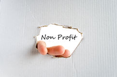 Non Profit. Hand and text Non Profit for text on the cardboard background - business concept stock photography