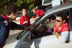Non-respect des distances de sécurité : L'homme arrive dans la voiture à la fête d'avant-match Images libres de droits