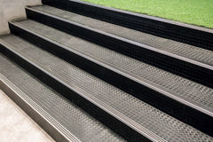Non-slip stairs with dot pattern close up for background. Artificial grass lawn floor across with black rubber stairs Royalty Free Stock Photography