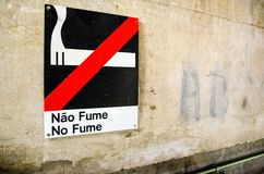 Non smoke plate in a wall. Non smoke plate in a old wall written in two languages royalty free stock image