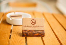 This is a non-smoking room sign. A non-smoking room sign on wooden table at hotel balcony stock photography