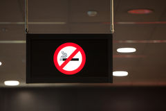 Non smoking sign hanging from the ceiling. A black, illluminated non smoking sign with a red smoking not permitted or don't smoke iconic message hangs from a Stock Photos
