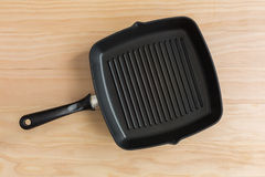 Non stick grill pan. On wooden background Royalty Free Stock Images