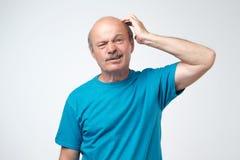 Non sure Adulto maturo in maglietta blu che ha un dubbio fotografia stock libera da diritti