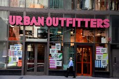 Non western man walks by Urban Outfitters stock photo