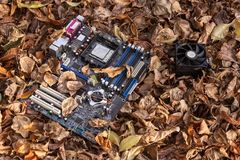 Non-working computer motherboard thrown into the street. Non-working computer motherboard thrown on the street in autumn in the fallen leaves royalty free stock photos