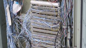 Non-working Electric Switchboard with Protruding Network and Telephone wires on the street. A pile of tangled wires in the electro panel board. Thailand stock video
