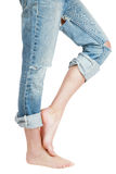Nonchalance. Long legs of slim barefoot girl in blue ragged grunge jeans Stock Photo