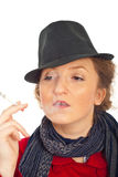 Nonchalant woman with hat smoking Royalty Free Stock Photos