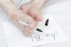 Nonconformist handwriting. Caucasian male writing alphabet using bare foot Stock Photos