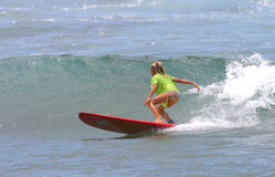 女孩夏威夷红色冲浪板冲浪的年轻人 免版税库存照片