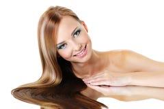 微笑美丽的女性光泽的头发直接 免版税库存图片