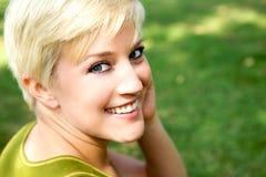美丽的白肤金发的女孩俏丽的微笑 免版税库存照片