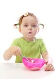 吃女孩酸奶的婴孩 免版税库存图片