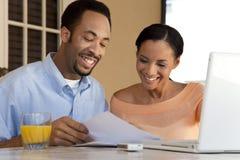 Ζεύγος αφροαμερικάνων που χρησιμοποιεί το φορητό προσωπικό υπολογιστή Στοκ εικόνα με δικαίωμα ελεύθερης χρήσης