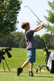 男孩打高尔夫球 库存照片