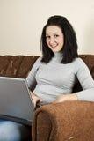 有膝上型计算机的微笑的少妇 库存照片